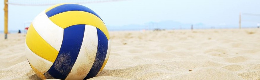 A blue, white, and yellow beach volleyball resting in a bed of golden sands.