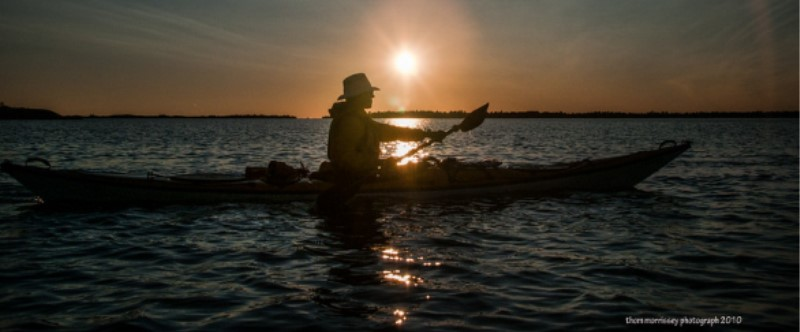 A kayaker paddling to the right side of the screen with a high sunset in the background