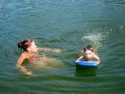 A swim instructor and student using a flutter board
